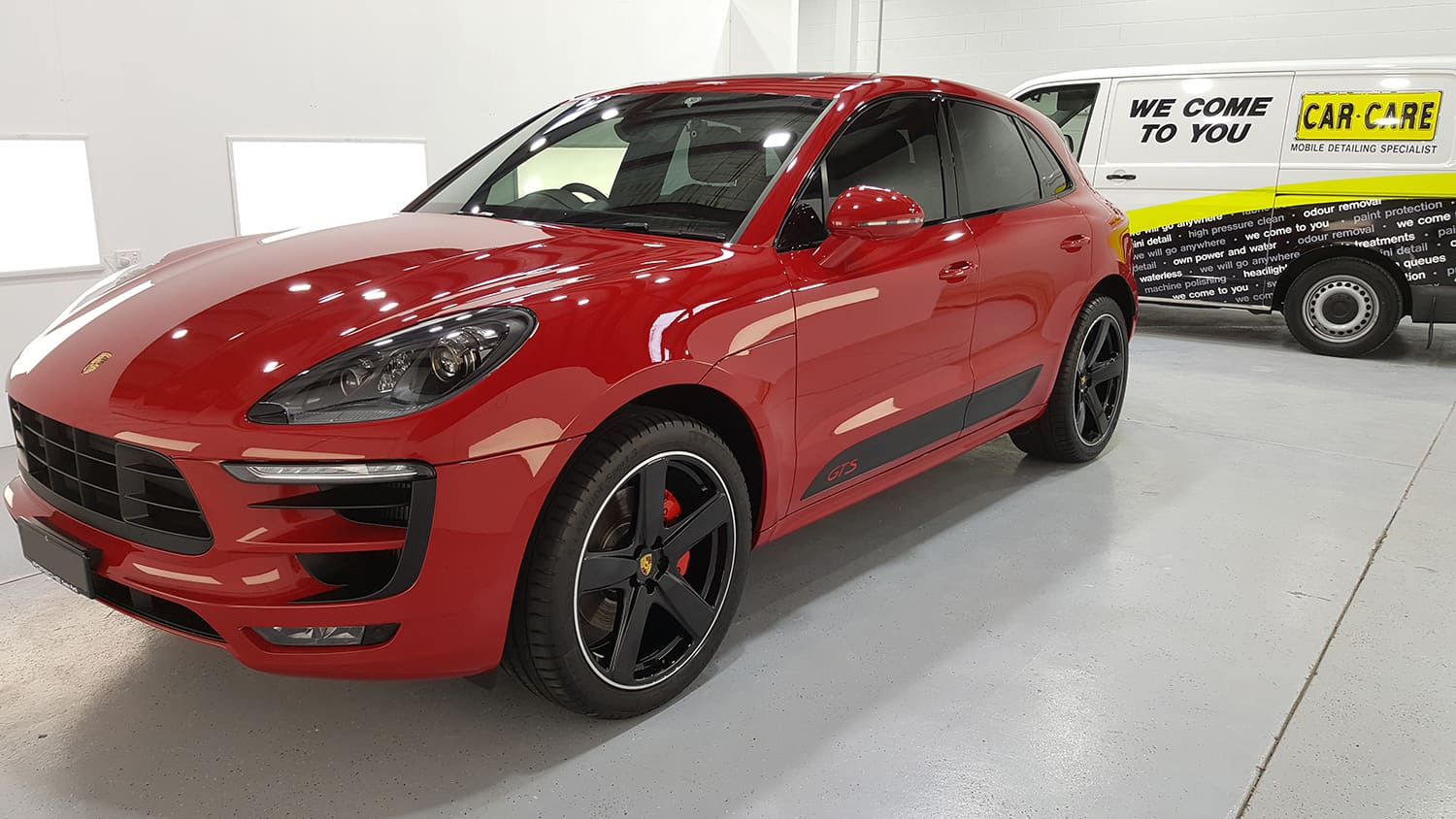 A freshly cleaned Red Porsche Macan S, that has had a full car detailing service on it, in a showroom