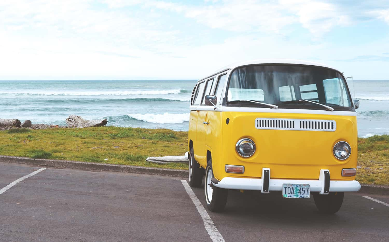 A Freshly Detailed & Clean Yellow VW Camper Van in a Car Park on the Coastline